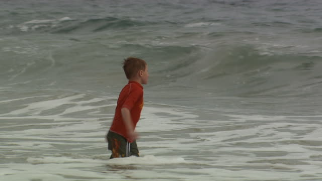a boy playing in the surf - see other clips from this shoot 1156 stock videos & royalty-free footage