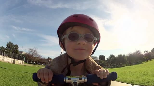 pov of a boy riding a scooter at a park. - model released - 1920x1080 - hd - push scooter stock videos & royalty-free footage