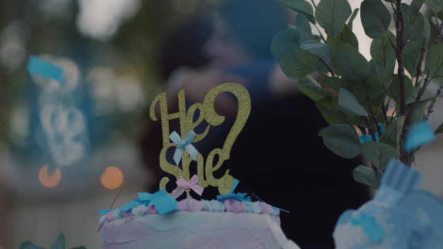 slo mo. cu of a cake at a gender reveal party with a he, she cake topper with blue confetti falling - baby shower video stock e b–roll
