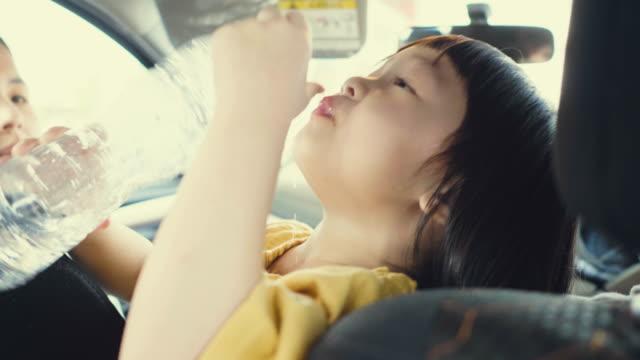 en bilbarnstol för barn dricker vatten - vattenflaska bildbanksvideor och videomaterial från bakom kulisserna