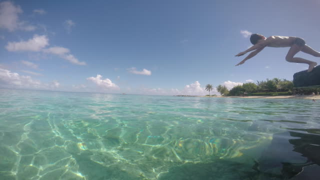 a child dives into the sea and swims - tahitian culture stock videos and b-roll footage