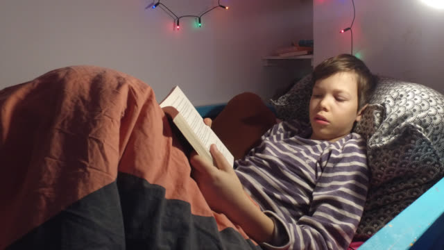 vidéos et rushes de a child reads a book in his bed in the evening. day of an 11 year old child at home due to school closures and confinement because of the coronavirus... - confinement