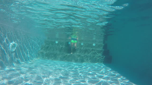 vídeos y material grabado en eventos de stock de a child swimming in a swimming pool - gafas de natación