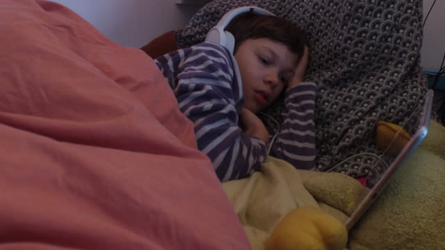 a child watches a film on a tablet, with headphones on his ears, in the evening. day of an 11 year old child at home due to school closures and... - digital tablet stock videos & royalty-free footage