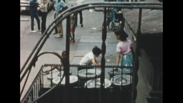 of a city sidewalk in new york's lower east side. in the background are african american children milling about. in the foreground, latino children... - lifestyles stock videos & royalty-free footage