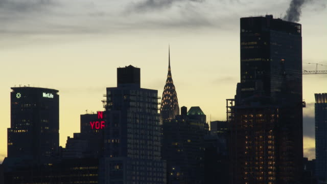 A CU of a cluster of buildings including the Chrysler Building, 1 Penn Plaza and the Met life Building, the buildings are in silhouette early dawn.