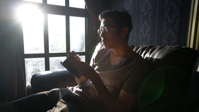 a concentrate man is reading,writing a note/ book / paper with tension in a low light room