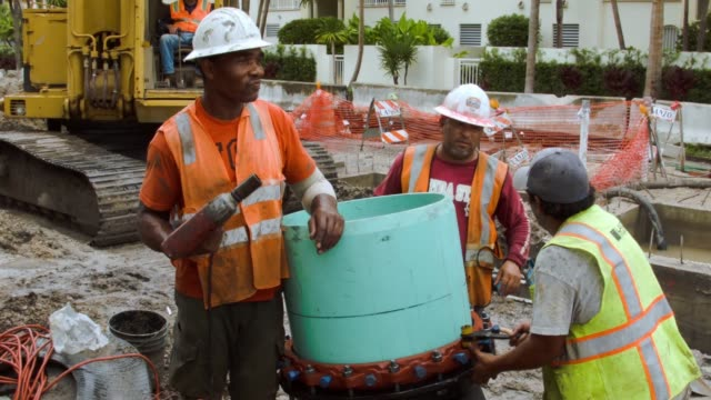 vídeos de stock, filmes e b-roll de ms a construction crew is working on installing drainage pipes and a water pump station in the street on september 25 2014 in miami beach florida as... - drenagem
