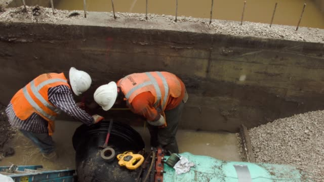 a construction crew is working on installing drainage pipes and a water pump station in the street on september 25, 2014 in miami beach, florida. as... - drainage stock videos & royalty-free footage