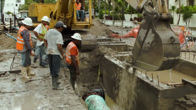 vídeos de stock, filmes e b-roll de ws< a construction crew is working on installing drainage pipes and a water pump station in the street on september 25 2014 in miami beach florida as... - drenagem