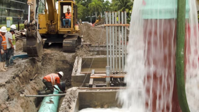 vídeos de stock, filmes e b-roll de ws a construction crew is working on installing drainage pipes and a water pump station in the street on september 25 2014 in miami beach florida as... - drenagem
