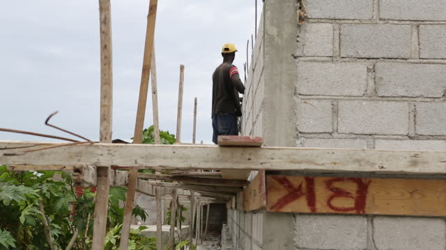 of a construction worker with a yellow hat who is working on a massive wall while he is attaching long metal wires to the wall for building a house.... - アフリカ系カリブ人点の映像素材/bロール
