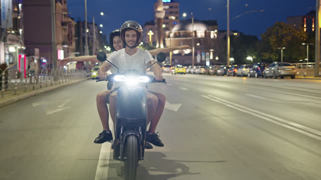 vidéos et rushes de one night in sofia - a couple cruising on rented e-scooter through the city of sofia while night. - sofia