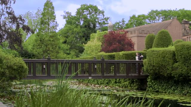 a couple in love walk across an ornamental bridge