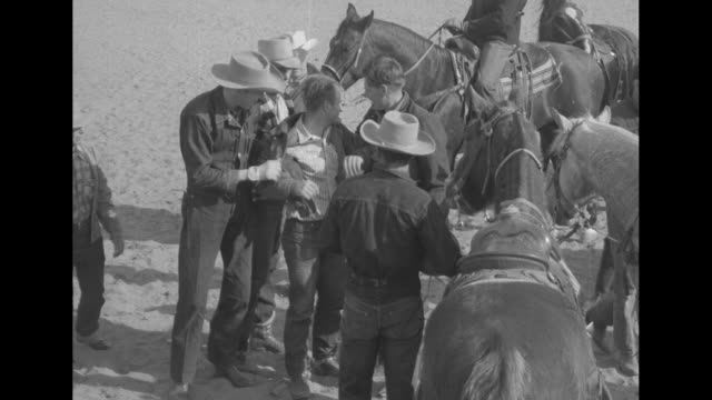 vídeos de stock e filmes b-roll de a cowboy runs forward with a basketball as others chase him and he hands off ball / the men attend to a fallen player who then unsteady rises / two... - jaqueta jeans