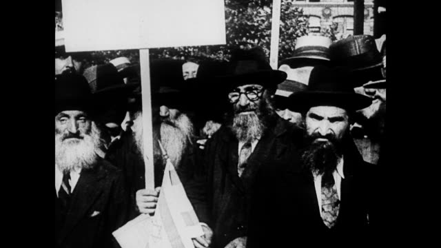 / a crowd of orthodox jewish men stand on stone steps / military parade goes marching by / jewish man holds up israeli flag orthodox jews watch... - 1935 stock videos & royalty-free footage