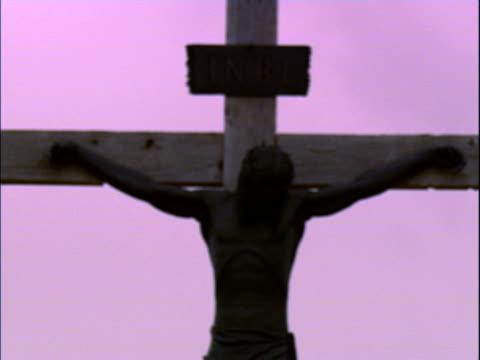 vídeos de stock, filmes e b-roll de a crucifix, zoomed out of focus - figura masculina
