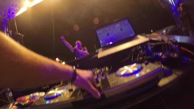 POV of a DJ behind the mixing table during a concert