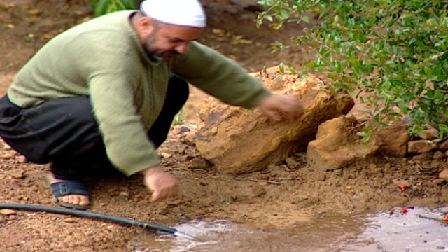 of a druze farmer watering and tending to an orchard. the skull cap of the farmer indicates that he is a juhhal, aka an uninitiated devotee in the... - irrigation equipment stock videos & royalty-free footage