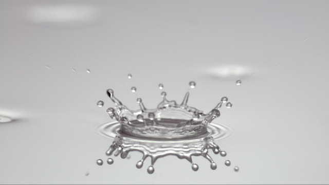 a falling single waterdrop creates a crown of droplets - splashing droplet stock videos and b-roll footage