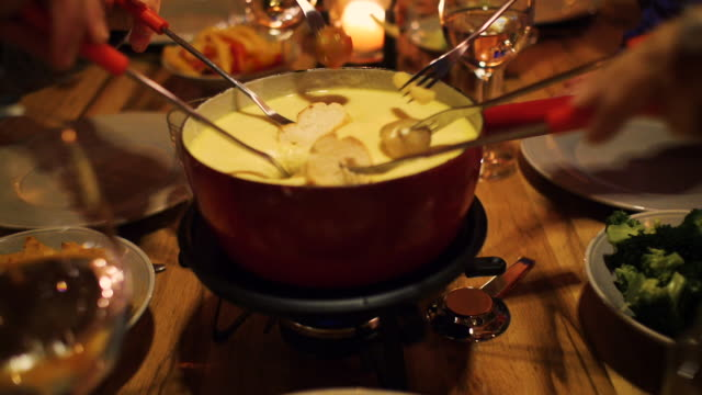 a family enjoying cheese fondue and they stick bread in the melted cheese in a cabin lodge setting - french food stock videos & royalty-free footage