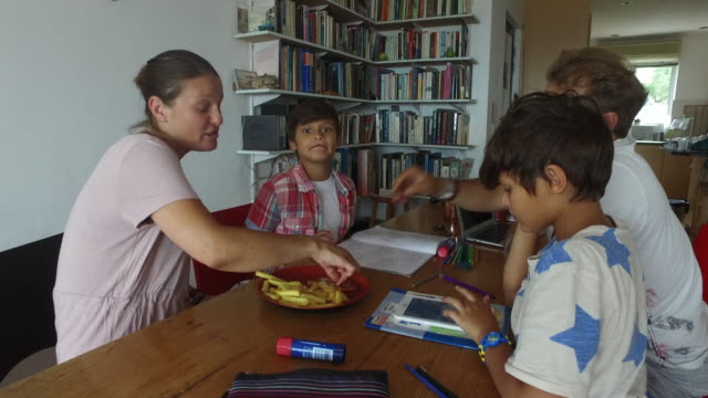 a Family snacking on potato chips while sitting around the table at home.