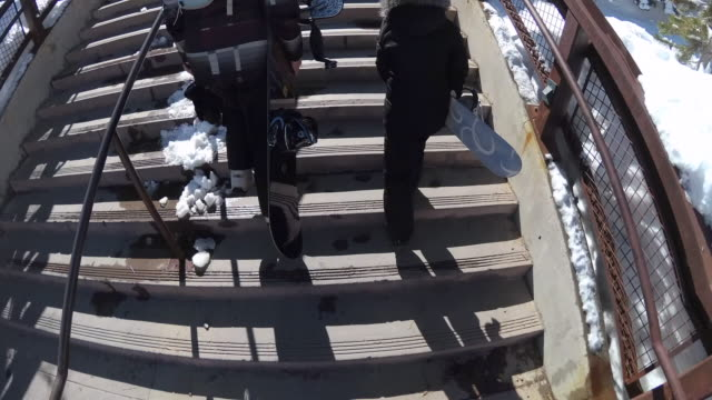 pov of a family walking with their snowboards at a ski resort. - ウィンターコート点の映像素材/bロール