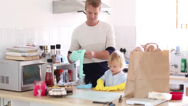 a father and son disinfecting the groceries. - cleaning glove stock videos & royalty-free footage