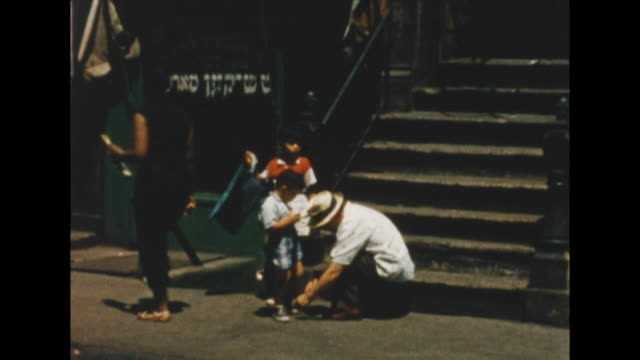 of a father fixing his son's shoe as another boy watches. african american women walks by. hebrew lettering in store window. new york's lower east... - judaism stock videos & royalty-free footage