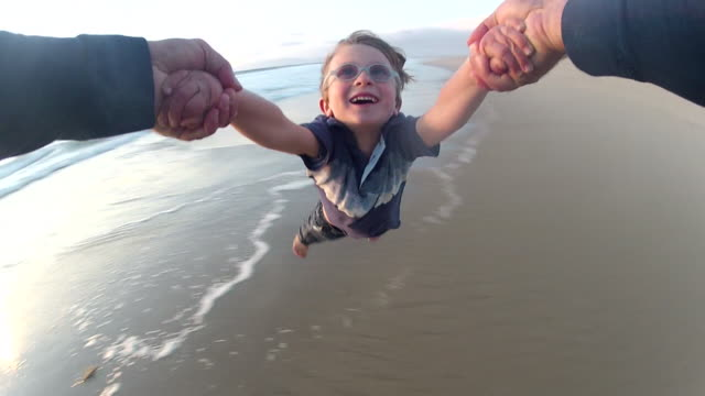pov of a father holding his son's hands and spinning him around on the beach at sunset. - model released - 1920x1080 - hd - boys stock videos & royalty-free footage