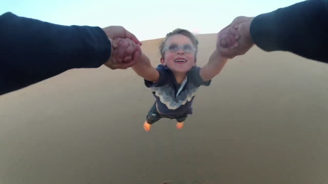 pov of a father holding his son's hands and spinning him around on the beach at sunset. - slow motion - model released - 1920x1080 - hd - activity stock videos & royalty-free footage