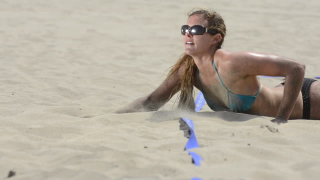 CU of a female beach volleyball player diving for the ball.