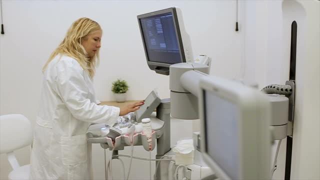 vídeos de stock, filmes e b-roll de um radiologista feminino prepara um moderno scanner 3d ultra sônico para exame - ultrassom 3d