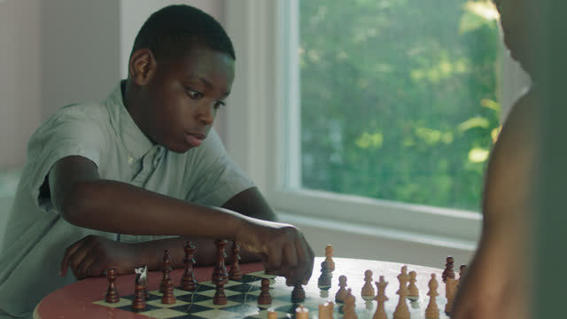 MS of a focused boy playing chess against mature man