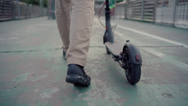 a freelancer ride modern electric scooters to work at sunrise - scooter stock videos & royalty-free footage