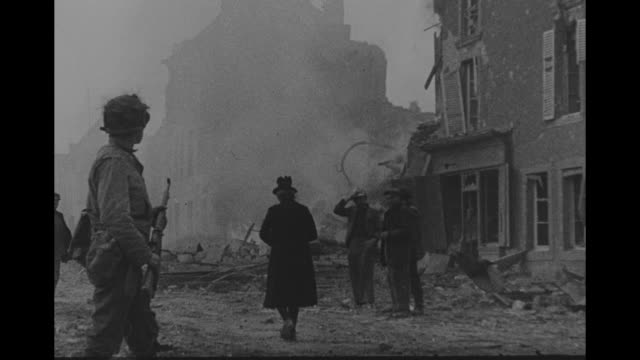 vidéos et rushes de a frenchman assembles possessions in bombed-out street as others add to his pile; old woman leaning heavily on a cane hobbles on street with... - seconde guerre mondiale