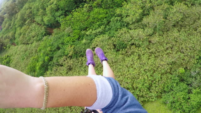 pov of a girl racing down a zipline with her feet stretched out - turtle bay hawaii stock videos and b-roll footage