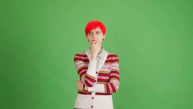 a girl with red hair thinks and an idea comes to her on a green background - blouse stock videos & royalty-free footage
