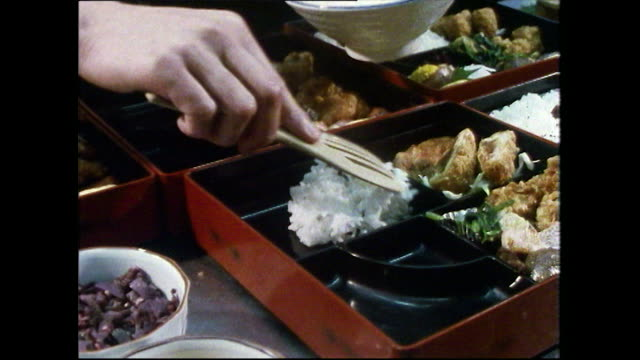 cu of a gourmet bento box being packed using chopsticks; 1989 - sticky stock videos & royalty-free footage