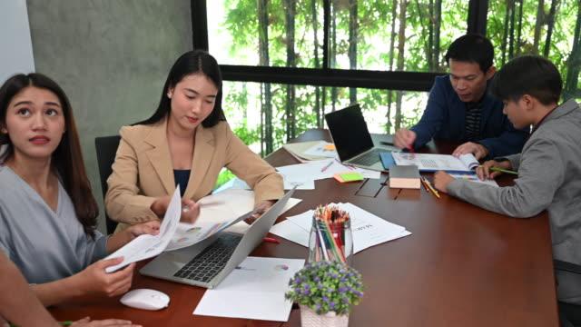 vídeos y material grabado en eventos de stock de un grupo de mujeres de la oficina de negocios asiáticas discutiendo ideas mientras trabajan en la oficina - desk