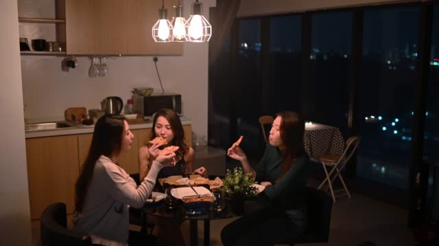 a group of asian chinese female friends having social gathering in apartment eating pizza in dining room at night - dining room stock videos & royalty-free footage