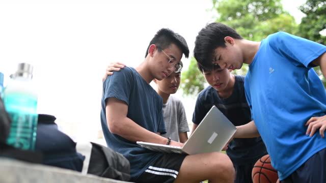 vídeos y material grabado en eventos de stock de un grupo de adolescentes chinos asiáticos al lado de la cancha de básquetbol teniendo discusión y reunión después del juego - rodear