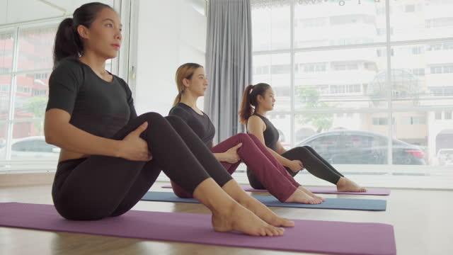 un gruppo di amiche asiatiche esercitano in classe pilates sdraiato su tappetini che si estendono in palestra. - pilates video stock e b–roll