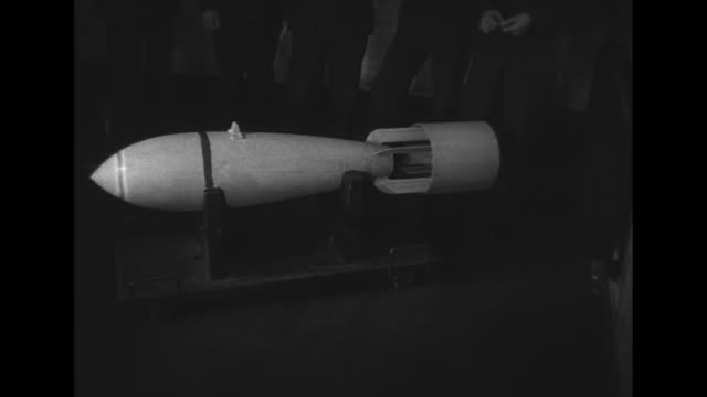 of a group of bombs / white bomb on a stand / overhead view of a group of bombs / a trailer loaded with bombs being pulled / british royal air force... - 爆撃機点の映像素材/bロール