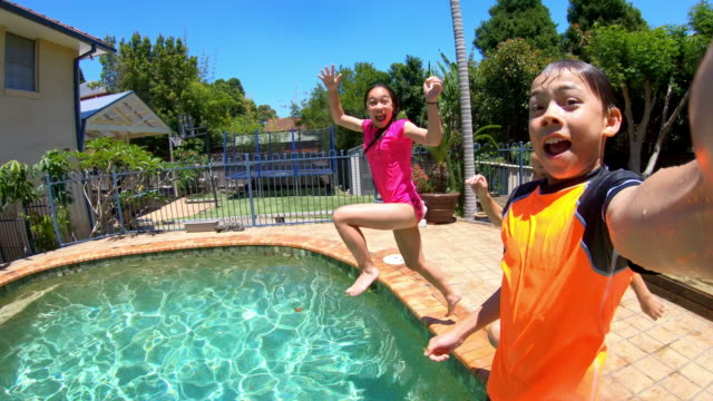 pov of a group of children jumping in a swimming pool - pool stock videos & royalty-free footage