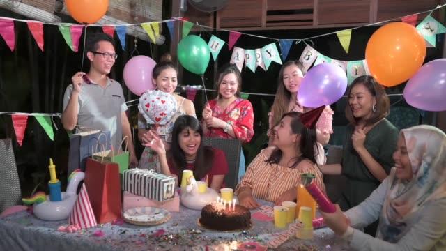 stockvideo's en b-roll-footage met een groep van multi-ethiek vrienden vieren verjaardagsfeestje in een traditioneel maleis huis - feestmuts