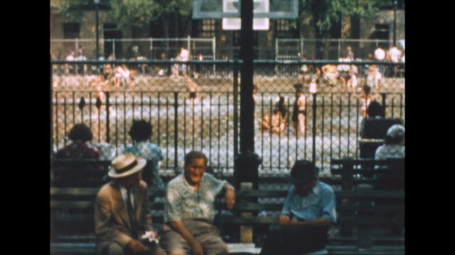 of a group of old men in new york's lower east side playing a card game in front of a flooded basketball court. humorous sideview of a little boy... - summer stock videos & royalty-free footage