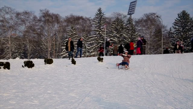 a group of people and children Tobogganing