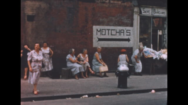 "vídeos y material grabado en eventos de stock de of a group of people sitting in the shade by an apartment building in new york's lower east side. ads for ""radio / television motorola"" and a sign... - motorola"