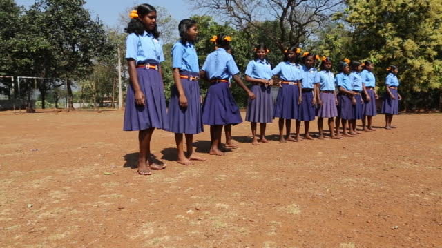 ws of a group of schoolgirls in school uniforms lined up and divided in two teams on a football field at a school in the village satia a small... - westbengalen stock-videos und b-roll-filmmaterial